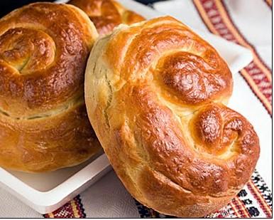Fresh baked dinner roll buns on white platter.